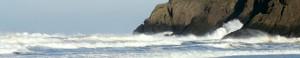 Waves crash into a large rock